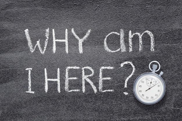 Waarom ben ik hier vraag geschreven op schoolbord met vintage nauwkeurige stopwatch Premium Foto