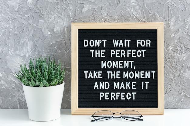 Wacht niet op het perfecte moment, neem het moment en maak het perfect. motiverende citaat op letter board, sappige bloem Premium Foto