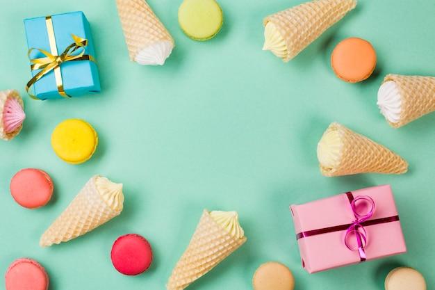 Wafel kegels; bitterkoekjes en ingepakte geschenkdozen op mintgroene achtergrond Gratis Foto