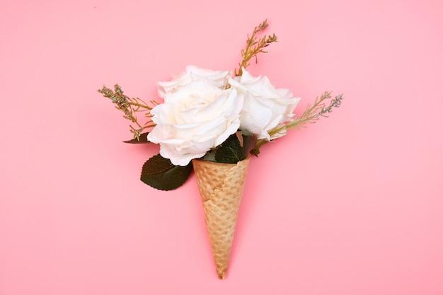 Wafelkegel met bloemen op roze. Premium Foto