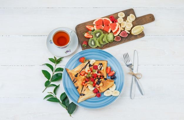 Wafels en fruit in blauw bord met fruit Gratis Foto