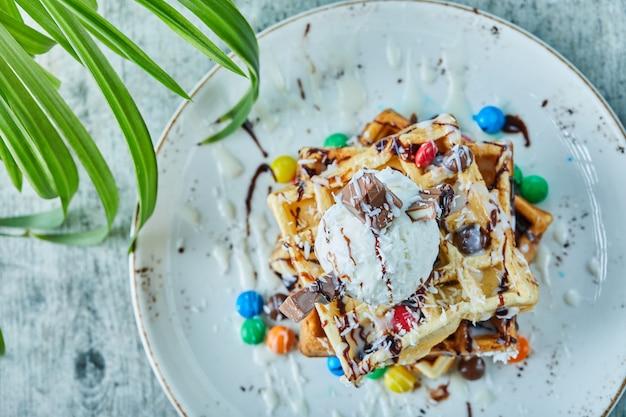 Wafels met ijs, snoep, chocolade in de witte plaat op het bladoppervlak Gratis Foto