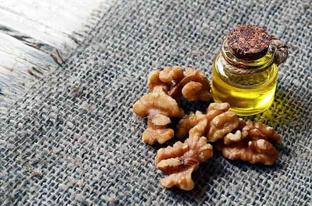Walnotenolie met gepelde walnoten op jute doek Premium Foto