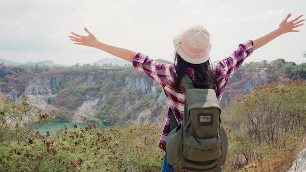 Wandelaar aziatische backpacker vrouw lopen naar de top van de berg, vrouw geniet van haar vakantie op wandelen avontuur gevoel vrijheid. Gratis Foto