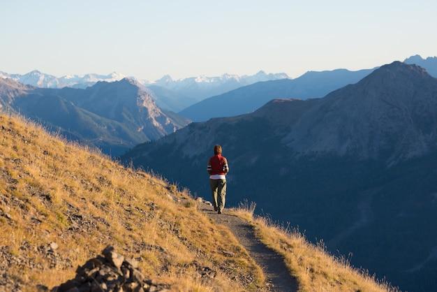 Wandelaar in landschap van de hoge hoogte het rotsachtige berg. zomeravonturen op de italiaanse franse alpen, Premium Foto