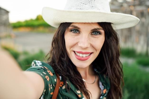 Wandelaar jonge vrouw die een selfiefoto in openlucht neemt Premium Foto