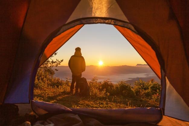Wandelaar staan op de camping in de buurt van oranje tent en rugzak in de bergen Gratis Foto