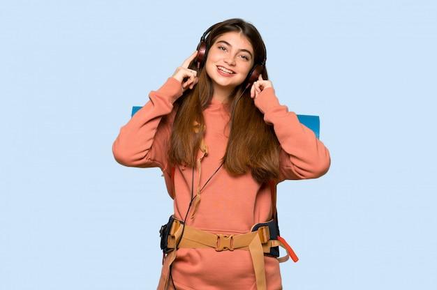 Wandelaarmeisje die aan muziek met hoofdtelefoons op blauw luisteren Premium Foto