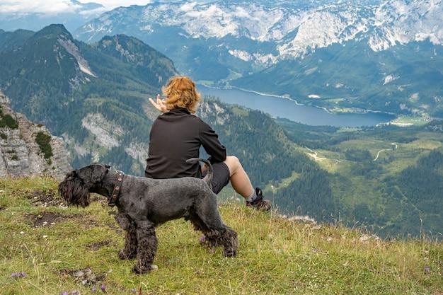 Wandelaars in de oostenrijkse alpen lopen op bergwandelpaden in het bos rond de meren met zwarte hond Premium Foto