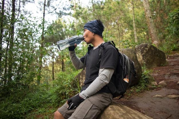 Wandelen man ontspannen en drinkwater uit de fles na een trektocht in de bergen Premium Foto