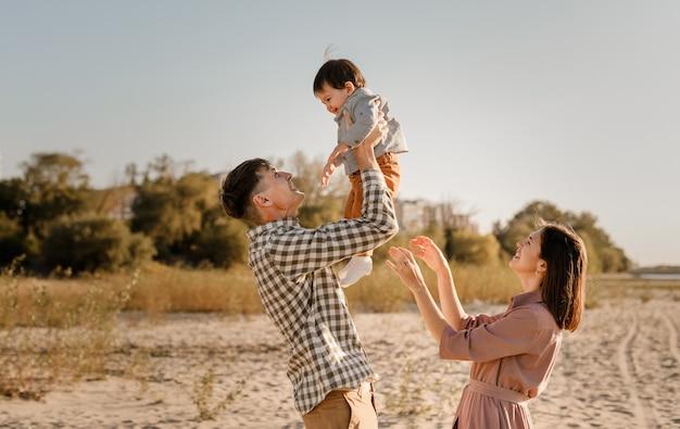 Wandelen op het zandstrand van de rivier en gelukkige familie. vader, moeder zoontje op handen houden en samen gaan. achteraanzicht. familiebanden concept. Premium Foto