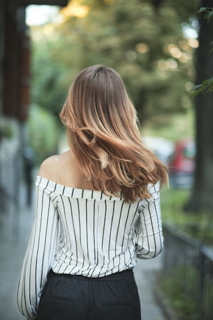 Wandelende vrouw met haar mooie haren in beweging Gratis Foto