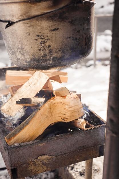 Wandelpot in het vreugdevuur. koken in de winter in de buurt van de rivier. Premium Foto