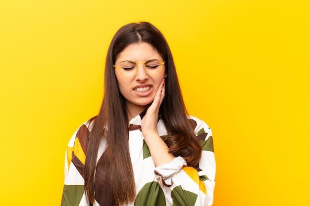 Wang vasthouden en pijnlijke kiespijn hebben, zich ziek, ellendig en ongelukkig voelen, op zoek naar een tandarts Premium Foto