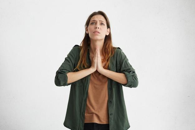 Wanhopige bezorgde jonge blanke vrouw met smekende smekende blik, hand in hand in gebed en god om vergeving te vragen. portret van spijtige ongelukkige vrouw handen samen te drukken tijdens het bidden Gratis Foto