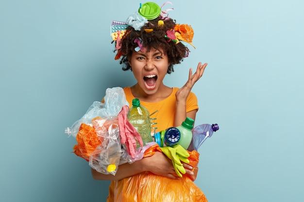 Wanhopige jonge afro-amerikaanse vrouw die vervuiling beu is, vuilnis opruimt, vecht tegen plastic besmetting, gekleed in casual t-shirt, boos gebaren, geïsoleerd tegen blauwe muur. Gratis Foto