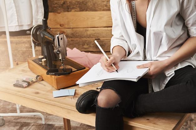 Wanneer hobby echt werk wordt. bijgesneden schot van creatieve vrouwelijke ontwerper van kleding zittend op tafel in de buurt van naaimachine in haar atelier, het maken van aantekeningen of het plannen van een nieuw ontwerp voor haar kledinglijn Gratis Foto