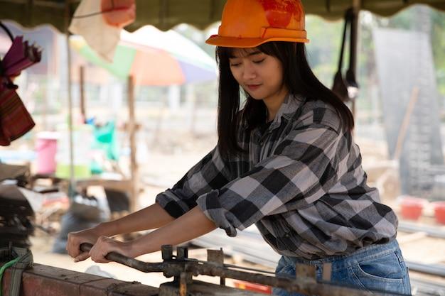Wapening die door arbeider op roestige kaliber in bouwwerf buigt Gratis Foto