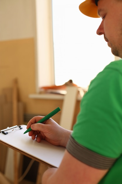 Wapens van arbeider die nota's over klembord met groene pen maken Premium Foto
