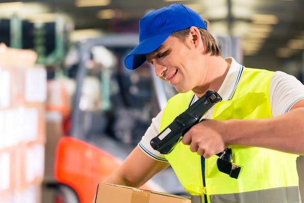 Warehouseman met beschermend vest en scanner, scant streepjescode van pakket, hij staat in magazijn van expeditiebedrijf Premium Foto