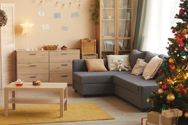 Warm-gestemde achtergrondafbeelding van gezellige woonkamer met kerstboom versierd met gouden details, kopie ruimte Premium Foto