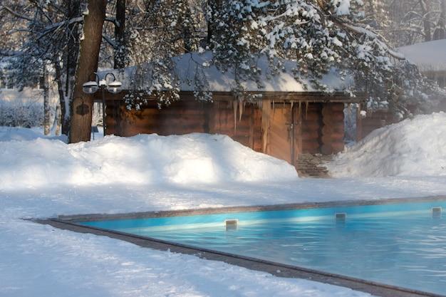 Warm zwembad met blauw water en houten russisch bad bij zonnig winterweer, buiten. Premium Foto