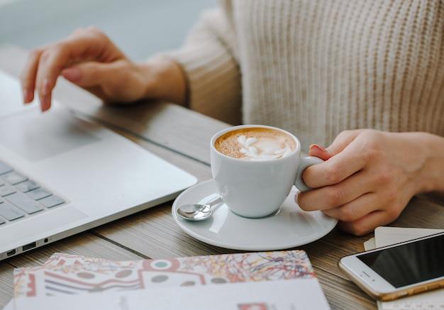 Warme cappucino met laptop op de tafel Gratis Foto