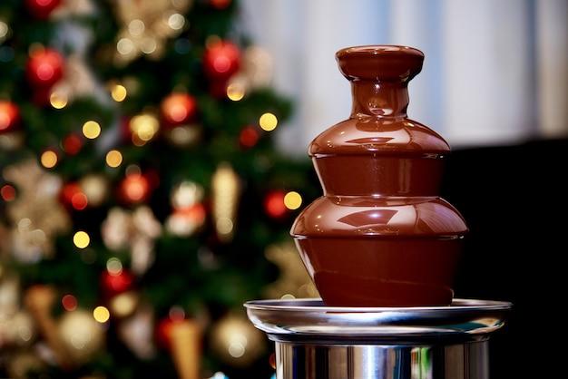 Warme chocoladefontein op de van de kerstboom. Premium Foto