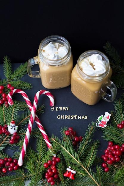 Warme chocolademelk en snoep marshmellou op de achtergrond van bomen. de inscriptie merry christmas Premium Foto