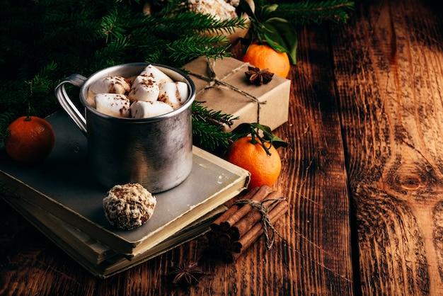 Warme chocolademelk met marshmallows en peperkoek over oude boeken Premium Foto