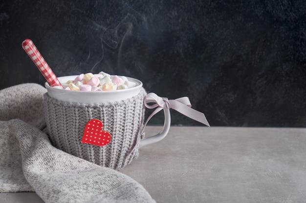 Warme chocolademelk met marshmallows, rood hart op de kop op tafel Premium Foto