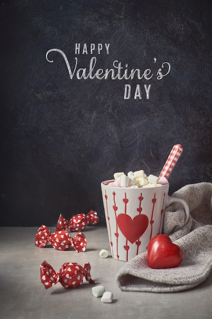 Warme chocolademelk met marshmallows, witte kop met hart op de tafel, groettekst Premium Foto