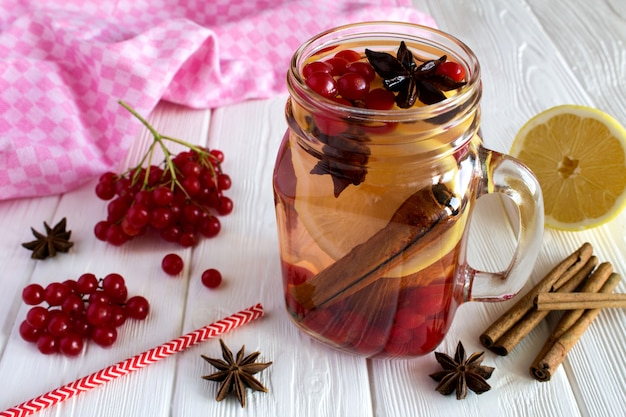 Warme drank met viburnum, citroen, kaneel en anijs op de witte houten achtergrond Premium Foto