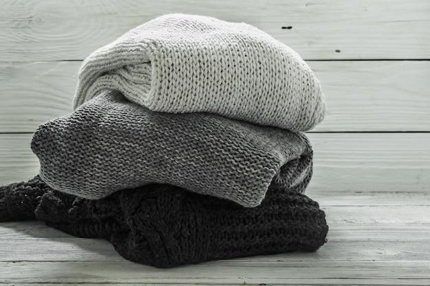 Warme gebreide trui, driedelig, zwart, grijs en wit op een houten muur Gratis Foto