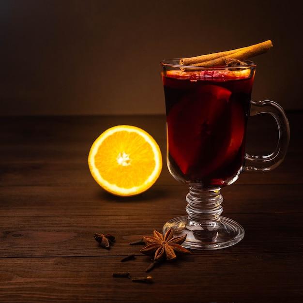 Warme kerstdrank glühwein met steranijs, kaneel en sinaasappel op houten tafel Premium Foto