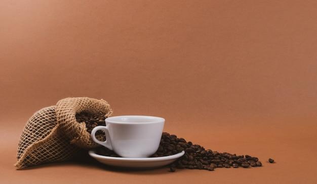 Warme koffiekopje en koffiebonen in jute zak Premium Foto