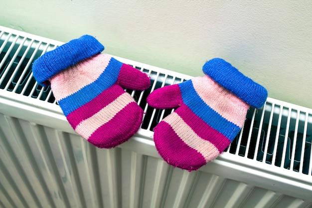 Warme, met de hand gebreide gestreepte wollen handschoenen voor kinderen die op hoofd drogen Premium Foto