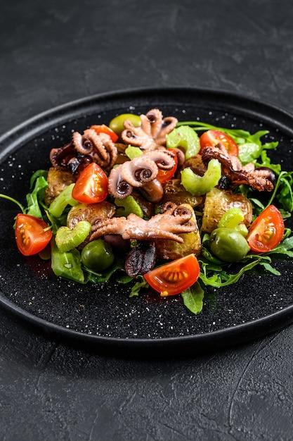 Warme salade met octopus, aardappelen, rucola, tomaten en olijven. zwarte achtergrond. bovenaanzicht Premium Foto