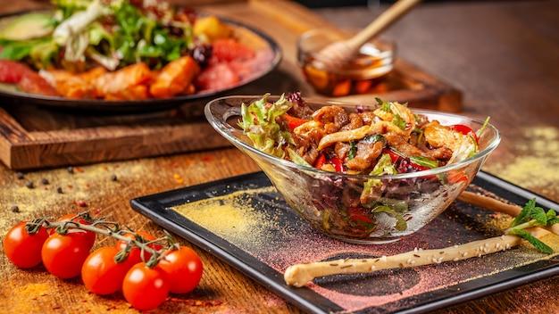 Warme salade met rundvlees en kip, paprika en honingmuntsaus. Premium Foto