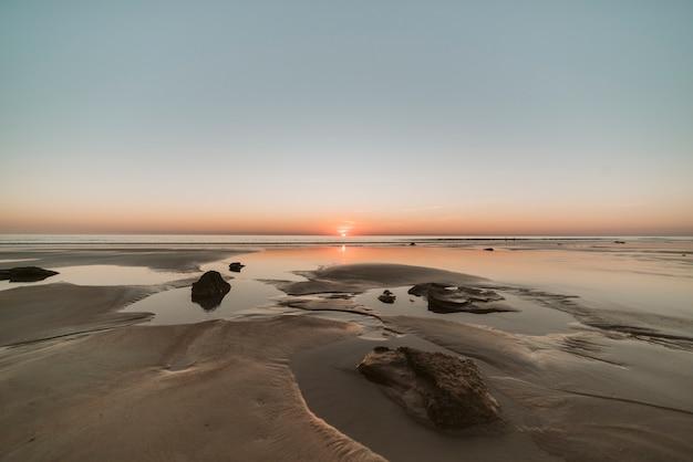 Warme zonsondergang in een uitstekend en beroemd australisch strand, bekend door zijn verbazingwekkende kleuren terwijl de zon ondergaat. Premium Foto