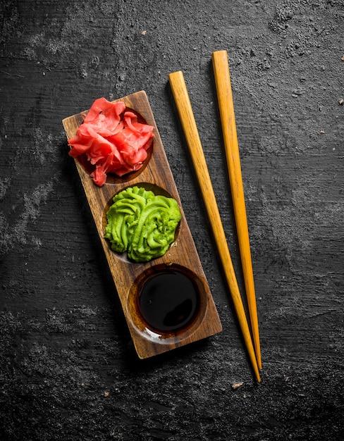 Wasabi, gemarineerde gember en sojasaus in een houten tribune met eetstokjes op zwarte rustieke lijst Premium Foto