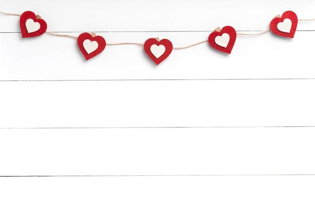 Wasknijpers met rode harten die op koord achter witte houten oppervlakte hangen. kopieer ruimte, bovenaanzicht. Premium Foto