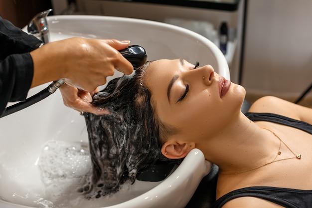 Wasprocedure. mooie jonge vrouw met het hoofd van de kapperwas bij haarsalon. Premium Foto