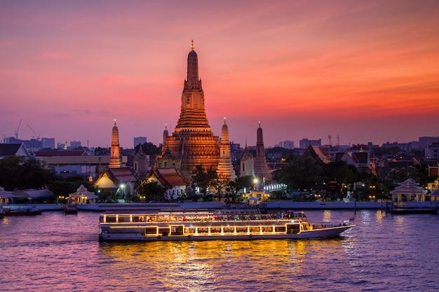 Wat arun en cruiseschip in zonsondergangtijd, de stad van bangkok, thailand Premium Foto