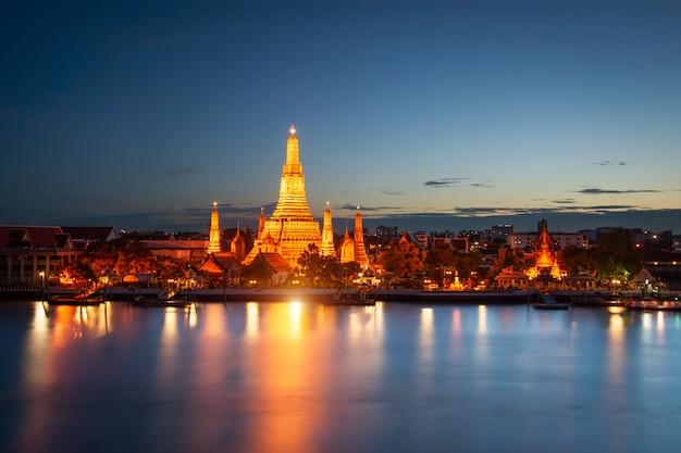 Wat arun over chao phraya river tijdens zonsondergang in bangkok, thailand Premium Foto