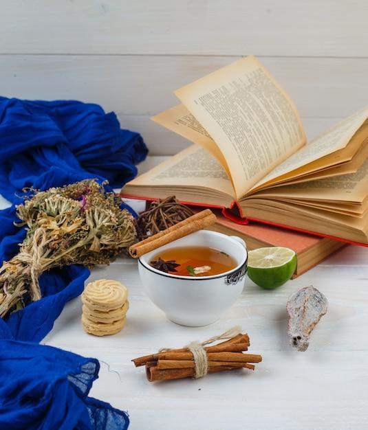 Wat kruidenthee, koekjes en bloemen met boeken, citroen, kruiden en blauwe sjaal Gratis Foto