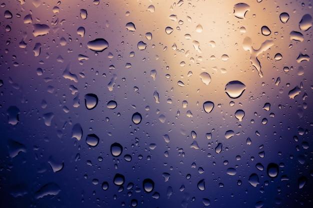 Water druppels achtergrond. kijk door het raam van een sterke regenachtige dag, ondiepe scherptediepte samenstelling en afgezwakt kleur. Premium Foto