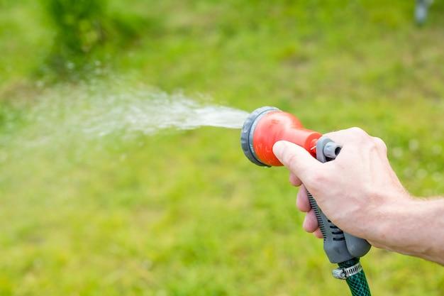 Water geven bedden en planten in de zomertuin van sprinkler.watering gazon gras met een douchekop hoofd. handmatige irrigatie irrigeert bloembedden, een groen gazon en bloeiende struiken. slang Premium Foto