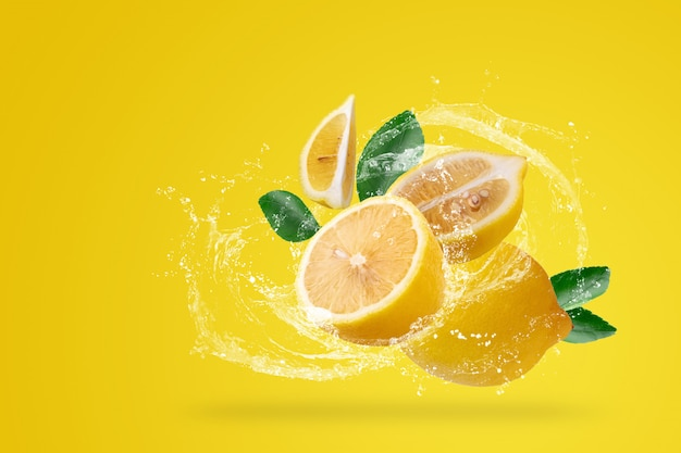 Water het bespatten en geel citroenfruit op een gele achtergrond. Premium Foto