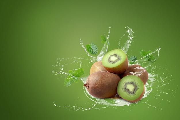 Water het bespatten op kiwifruit en half kiwifruit op groene achtergrond. Premium Foto